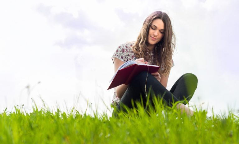 Beautiful young girl with a notebook siting down on lawn and smiling on a warm sunny day with copy space